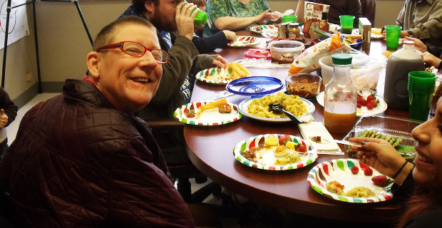 A group of people sits and eats at a table crowded with food and drinks. In the foreground, one woman turns over her shoulder to smiles broadly at the camera.