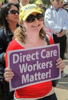 A grinning woman in sunglasses holds a purple sign that reads Direct Care Workers Matter