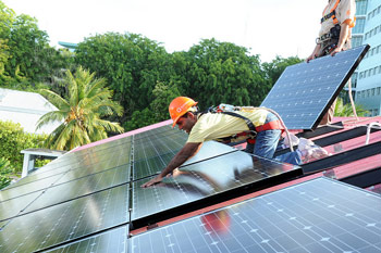 President Mohamed Nasheed of the Maldives installing solar panels on his roof